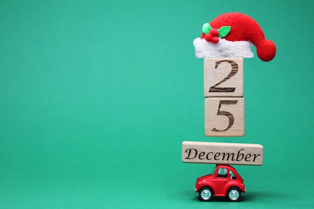 A small red toy car carrying december 25 on wooden blocks and a christmas hat on top of them.