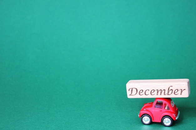 A small red toy car carrying a wooden block with the inscription december on its roof. green background. christmas and new year holidays are approaching.