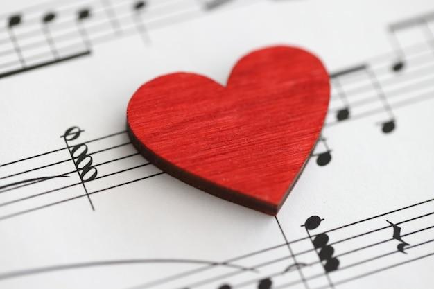 Маленькое красное деревянное сердце с музыкальными нотами любит изучать музыкальную концепцию