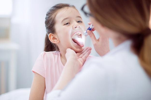 Небольшое покраснение. избирательный фокус очаровательной милой маленькой девочки, открывающей рот и смотрящей на женщину-врача, держащую фонарик