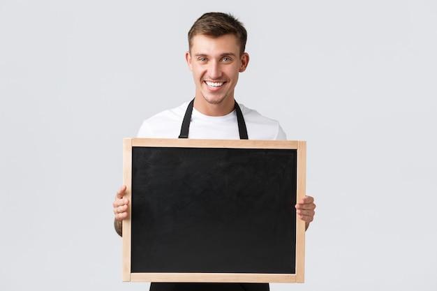 小規模小売業の所有者、カフェやレストランの従業員のコンセプト。フレンドリーでかっこいいセールスマンは、クライアントに何かを発表し、看板なしでボードを保持し、幸せな、白い背景に笑みを浮かべて