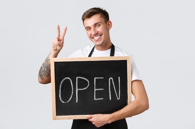 소규모 소매 비즈니스 소유자, 카페 및 레스토랑 직원 개념. 친절한 행복한 바리스타, 평화 사인을 보여주는 세일즈맨, 그리고 우리는 열린 사인이며 고객이 커피, 흰색 배경을 즐기도록 초대합니다.