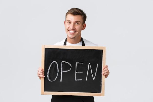 소규모 소매 비즈니스 소유자, 카페 및 레스토랑 직원 개념. 웃고 있는 친절한 웨이터, 우리가 열린 사인을 보여주는 바리스타, 손님 초대, 새로운 여름 프로모션, 흰색 배경