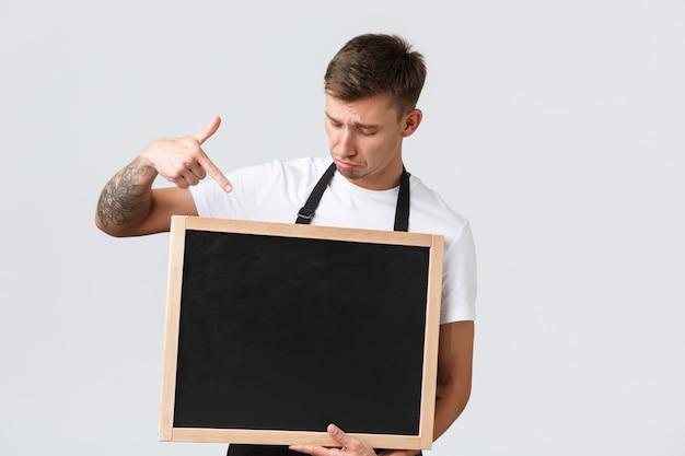 Владельцы малого розничного бизнеса, концепция сотрудников кафе и ресторанов. расстроенный мрачный и огорченный продавец, указывая пальцем на меловую доску без знаков, разочарованный стоящий белый фон.