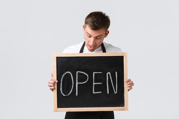 Proprietari di piccole imprese al dettaglio, concetto di dipendenti di bar e ristoranti. divertito venditore felice, cameriere informa sull'apertura, mostrando segno aperto e guardando ottimista, sfondo bianco