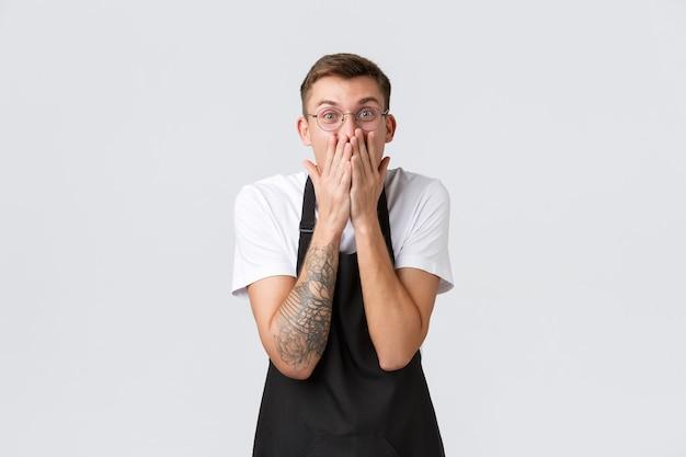 Proprietari di piccole imprese al dettaglio, concetto di dipendenti di bar e ristoranti. il cameriere felice eccitato e stupito reagisce a notizie incredibili, tiene le mani sulla bocca e sorride divertito, in piedi sullo sfondo bianco