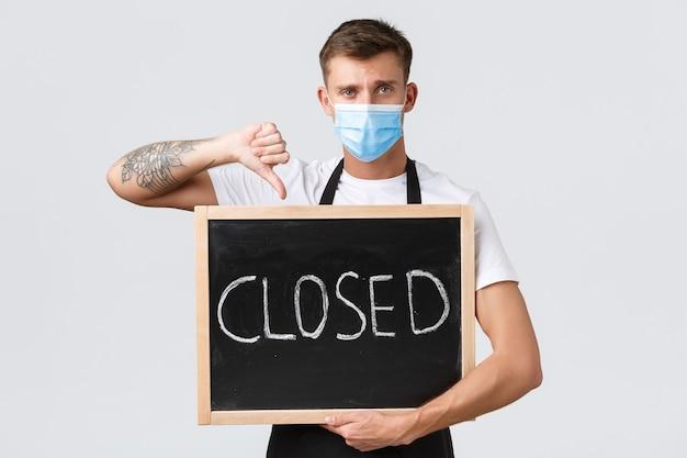 소규모 소매 업체 소유자, covid-19 및 사회적 거리 개념. 실망한 슬픈 바리스타, 의료용 마스크를 쓴 웨이터가 고객에게 레스토랑이 문을 닫았다는 사실을 알리면서 엄지손가락을 아래로 내리고 흰색 배경