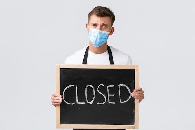 소규모 소매 업체 소유자, covid-19 및 사회적 거리 개념. 우울하고 화난 세일즈맨, 의료용 마스크를 쓴 웨이터는 카페가 문을 닫았다고 알리며 표지판을 보여주고 인상을 찌푸리고 실망했다