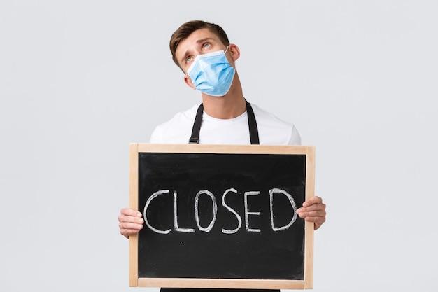 小規模小売業の所有者、covid-19および社会的距離の概念。悲しくて憂鬱なセールスマン、医療マスクのカフェの従業員が目を上げて閉じたサインを見せ、封鎖に失望した