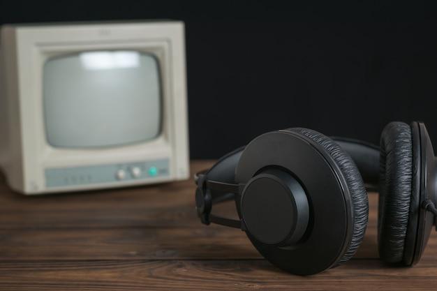 검정색 배경에 있는 나무 탁자에 있는 작은 복고풍 모니터와 헤드폰. 사운드 및 비디오 재생 기술.