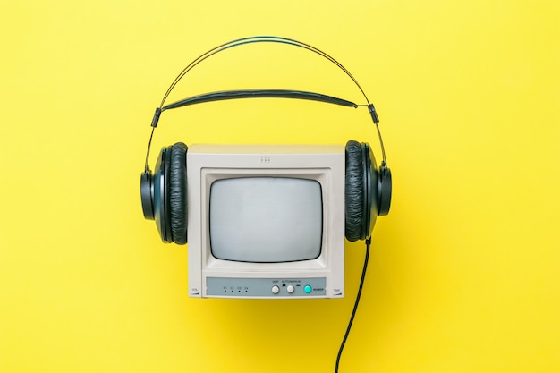 Маленькие ретро-мониторные наушники черного цвета на желтом фоне. техника воспроизведения звука и видео.