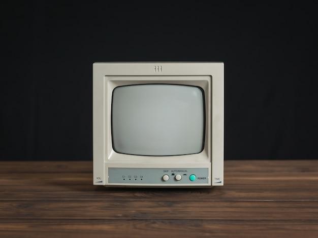 黒の背景に木製のテーブルの上の小さなレトロなモニター。古いビデオ監視装置。