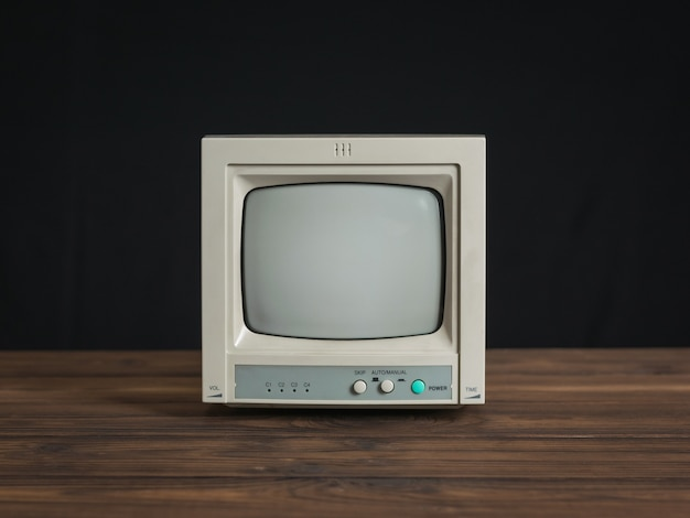 Small retro monitor on a wooden table on a black background. old video surveillance equipment.