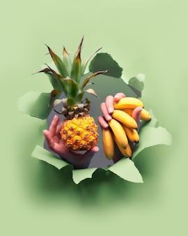 Маленький спелый апельсиновый ананас, куча маленьких бананов в руке. руки с фруктами показывают из разорванной бумажной дыры.