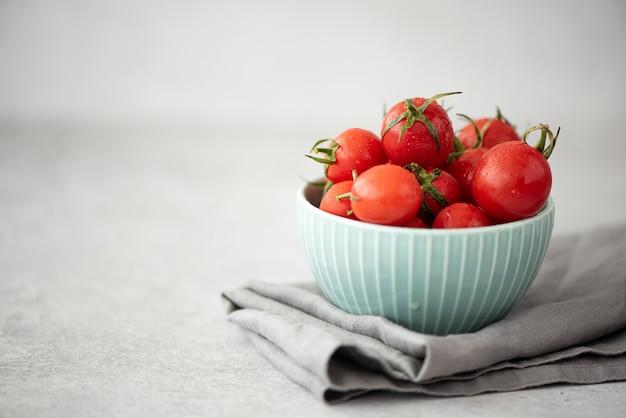 ターコイズブルーのボウルの枝に小さな熟した赤いチェリートマト