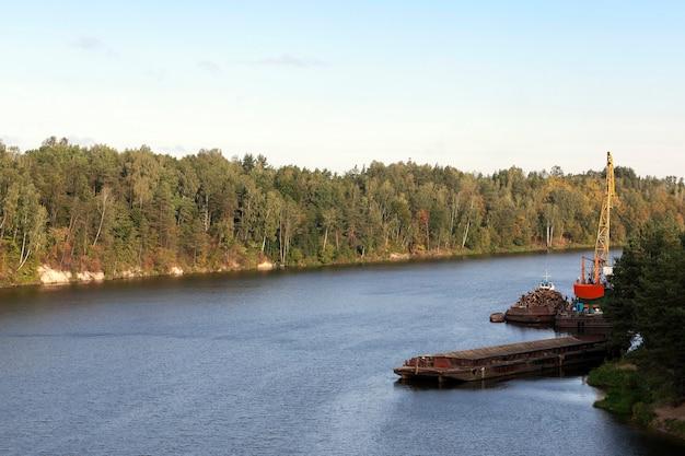 Небольшой речной порт, на территории которого лесозаготовка. летний пейзаж