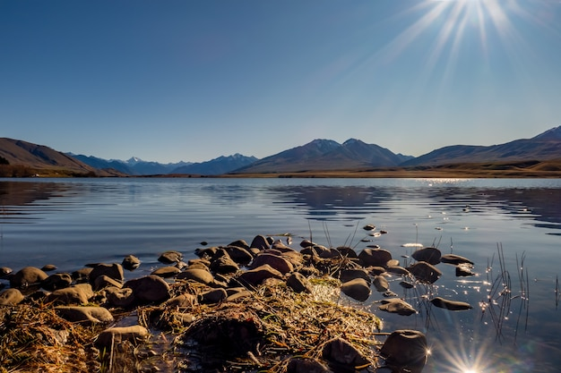 Small rocky promontory leading out to the calm lake with the southern alps