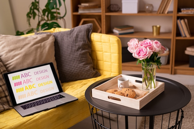 Small round black table with roses, cookies and cup of coffee standing by yellow sofa with pillows and laptop of designer in living-room
