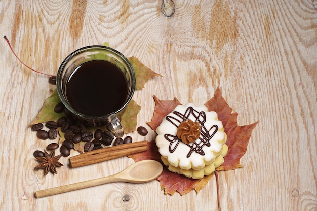 Small round cake, cup of coffee and autumn leaves on old wooden background