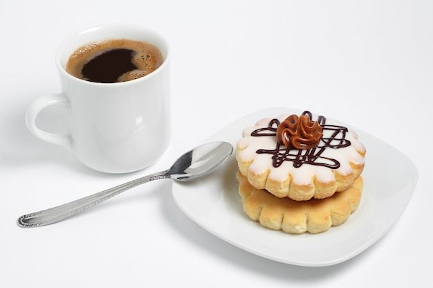 Small round cake with chocolate cream and cup of coffee on white background