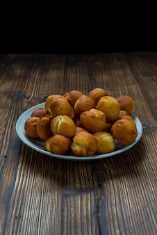Маленькие круглые пончики на деревянном столе