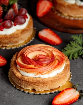 Small round pie decorated with cream and red apple slices