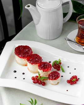 Small and round red currant cheesecakes plate