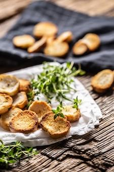 바삭한 식감과 황금빛 색감이 매력적인 작은 원형 짭짤한 미니 베이크 롤은 구운 빵을 종이나 행주에 타임과 함께 담아 제공합니다.