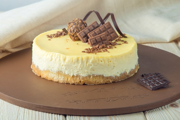 Small round vanilla cheesecake decorated with chocolate and truffle top