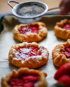 Small rustic strawberry galette pie tarts with powdering sugar on oven tray