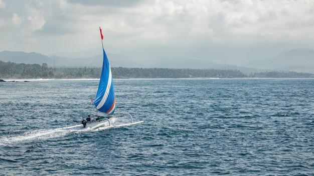 Piccola barca a vela galleggia sull'acqua con viste mozzafiato sulle montagne.