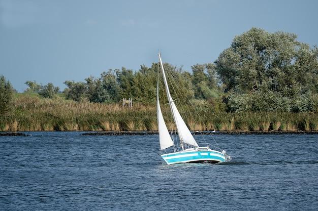 Маленькая парусная лодка на озере в окружении деревьев под солнечным светом