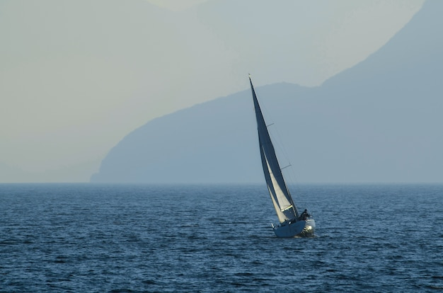 Small sailing ship on the sea surrounded by mountains covered in the fog at daytime