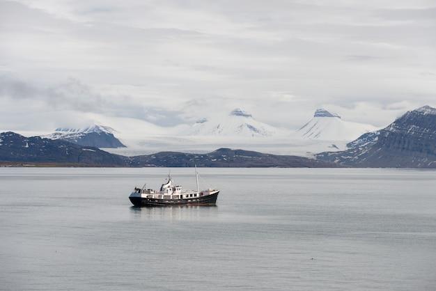 スバールバル諸島の美しい雪に覆われた山の小さな帆船