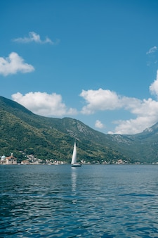 A small sailing yacht floats on the sea by the green mountains, blue sky and clouds
