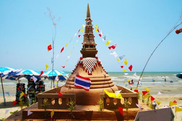 Маленькая пагода из песка на фестивале сонгкран представляет собой для того, чтобы забрать кусочки песка, прикрепленные к ногам из храма, чтобы вернуть храм в форме пагоды из песка.