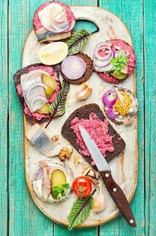 Маленькие бутерброды или брускетты с соленой сельдью и свеклой. открытый бутерброд с соленой сельдью.