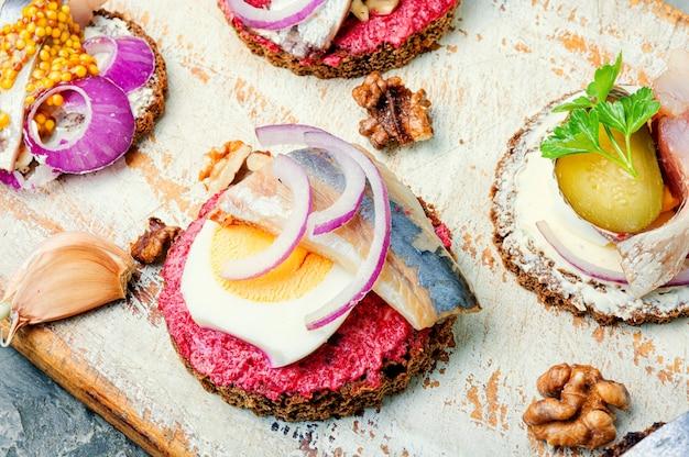 Маленькие бутерброды или брускетты с соленой селедкой, свеклой и луком