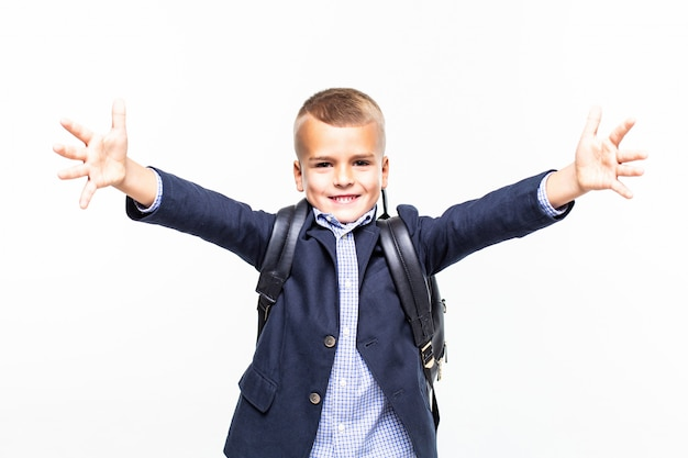 Small school boy making funny pose on white wall