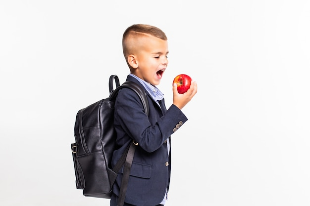 Small school boy with bag preparing to bite a big red apple and standing isolated on white wall