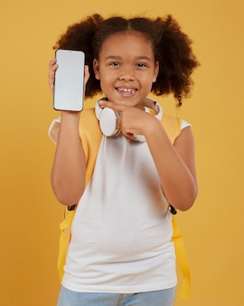 Small school girl showing empty mobile phone