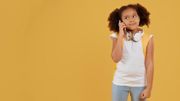 Piccola ragazza della scuola che parla sullo spazio della copia del telefono