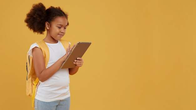 Small school girl using a digital tablet
