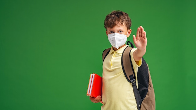 Small schoolboy with a backpack and books in a medical mask