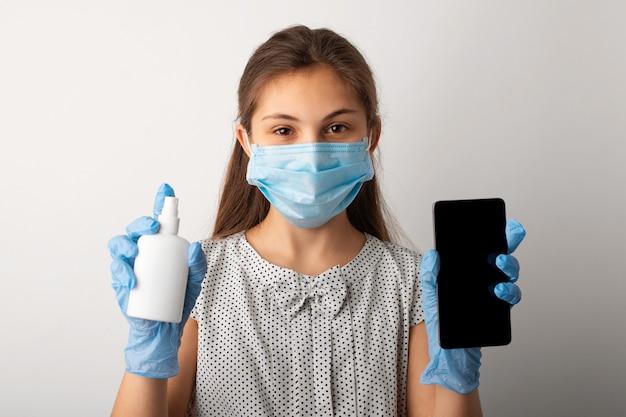 Маленькая школьница в медицинской маске и перчатках показывает в камеру мобильный телефон и бутылку с чистящей жидкостью