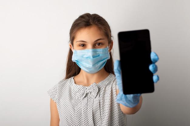 Маленькая школьница в медицинской маске и перчатках показывает мобильный телефон в камеру
