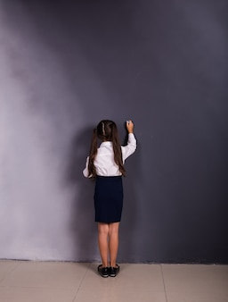 A small schoolgirl in a uniform stands with her back against a background with a slate