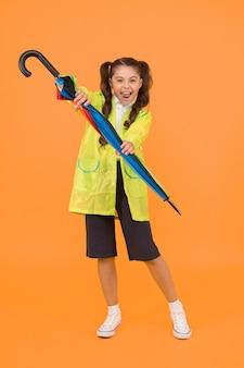 Маленькие школьницы носят водонепроницаемую одежду в дождливый день. симпатичная школьница чувствует себя защищенной от весенней погоды. водонепроницаемая концепция. совместите плащ с зонтиком. школьница носит плащ.