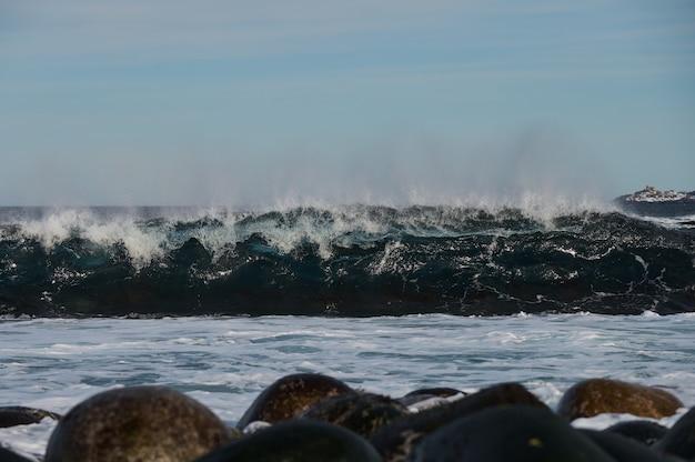 작은 파도가 해안의 돌에 부딪칩니다. 밝고 화창한 날과 파도의 하얀 거품.