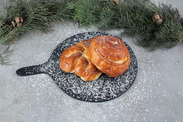 Piccolo tagliere con due panini accanto a rami di pino su superficie di marmo